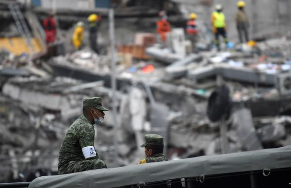 A man clad in fatigues gathers his composure as volunteers pick through the rubble of a building in Mexico City on Wednesday. The metropolitan area of some 20 million people saw at least 94 people die in Tuesday's earthquake, officials said.