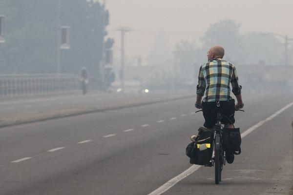 A bicyclist makes his way down Higgins Avenue in Missoula, Mont. as smoke from the nearby Lolo Peak Fire fills the air on Monday, Sept. 4, 2017. The air quality is has been measured at hazardous by the Montana Department of Environmental Quality. (Patrick Record/AP)