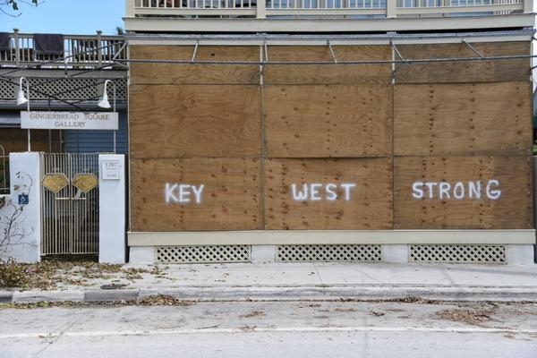 """A boarded up home with spray painted """"Key West Strong"""" along a debris strewn street, Key West, Florida, Sept. 15, 2017."""