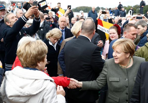 German Chancellor Angela Merkel (right) shakes hands with supporters as she arrives to address an election campaign rally of her political party, the Christian Democratic Union, in Kappeln, northern Germany, on Wednesday, during the final days before Germans vote for their next government.