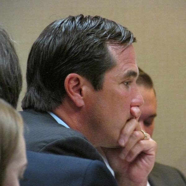 Michigan Health and Human Services Dept. Director Nick Lyon listens intently to testimony during his preliminary hearing