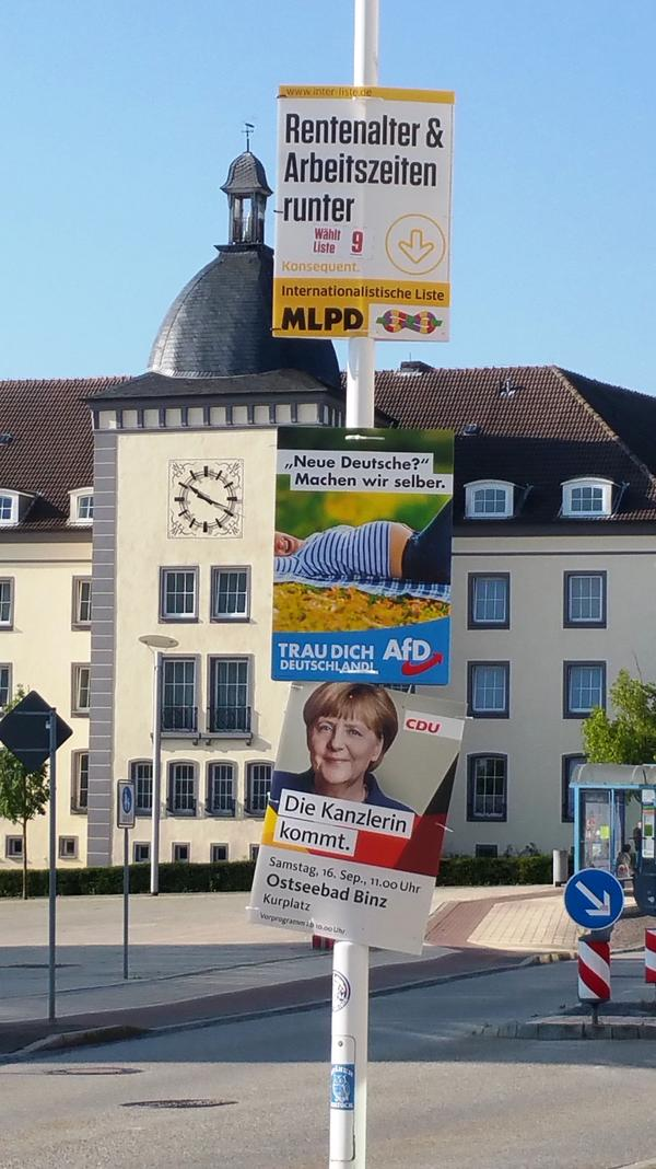 "In the eastern German city of Sassnitz, campaign posters promote (from top) a Marxist-Leninist party (""Lower retirement age and working hours""); the far-right Alternative for Germany (""New Germans? We will make them ourselves""); and Chancellor Angela Merkel (""The Chancellor is coming"")."