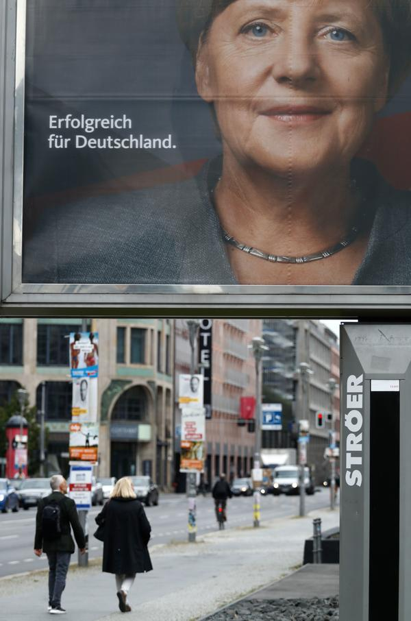 "Pedestrians in Berlin walk past an election poster for Merkel. The message on the poster reads ""Successful for Germany."""