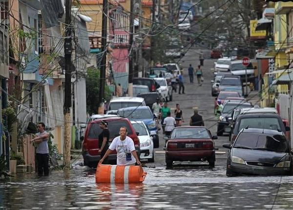 San Juan residents try to clean up flooded streets after Hurricane Maria hit Puerto Rico on Wednesday.