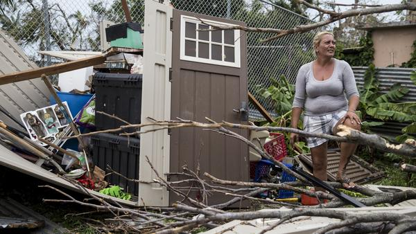 A resident faces the damage to her suburban San Juan property from Hurricane Maria. The lack of electricity and other key elements of infrastructure make recovery that much harder.