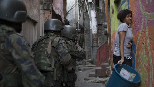 Soldiers pass a woman in an alley in the Rocinha favela of Rio de Janeiro on Friday, during an operation related to an apparent war among drug dealers.