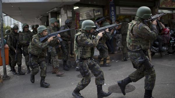 Soldiers enter Rio de Janeiro's Rocinha favela on Friday after shootouts erupted.