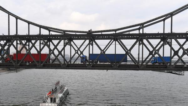 Trucks drive over the Friendship Bridge, from the North Korean town of Sinuiju to the Chinese border city of Dandong on Sept. 5. China says it will ban textile imports from North Korea.
