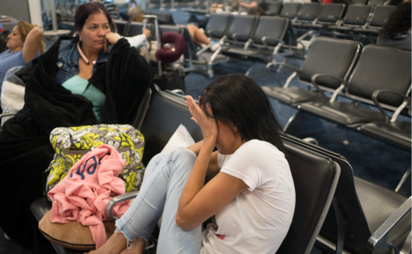 Nicole Castro, 25, daughter to Beth and Luis, shows her frustration as she waits at an American Airlines gate at Miami International Airport after their flight to Puerto Rico was canceled.