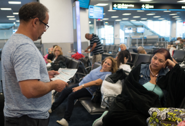 Luis Castro holds boarding passes in front of wife Beth Castro, after being rebooked on a Sunday flight at an American Airlines gate at Miami International Airport. The Castros, Puerto Ricans living in Killeen, Texas, are trying to get to the island to visit family affected by the destructive path of Hurricane Maria.