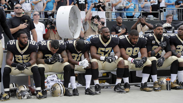 New Orleans Saints players sit on the bench during the national anthem before Sunday's NFL football game against the Carolina Panthers in Charlotte, N.C.