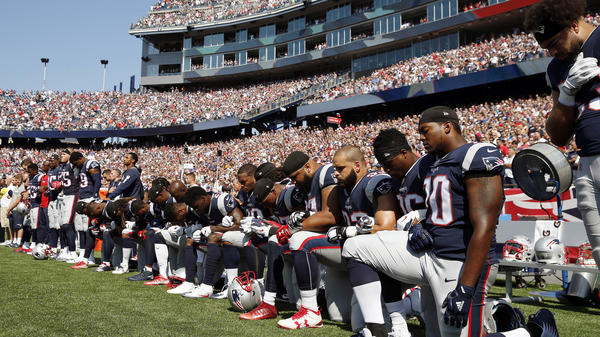 Several New England Patriots players kneel during the national anthem before an NFL football game against the Houston Texans.