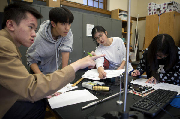 Slade Hu, 18 (from left), Steven Dai, 18, Echo Tian, 15, and Jessica Dia, 18, all of China, work on a project in Scott Burgess' AP Physics class at John Bapst High School in Bangor.