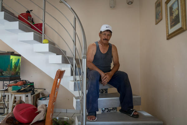 During the path of Hurricane Maria, Jose Torres kept repositioning the gas jugs behind him as the water rose inside his house. He is a diabetic and lost all his medications when his two-story house was flooded up to seven feet.
