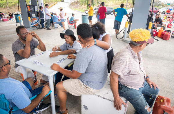 People play dominoes while waiting in line for gas. Authorities in Puerto Rico say there isn't a gas shortage. Instead, they say that distribution has been disrupted by the storm.