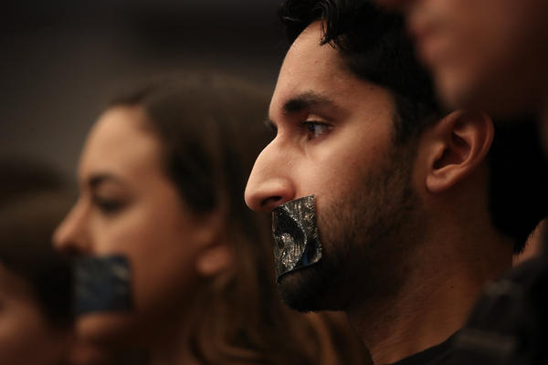 Georgetown University Law School students cover their mouths with tape to protest Sessions' speech on Tuesday.