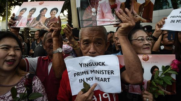 Supporters of former Thai Prime Minister Yingluck Shinawatra hold signs and images of her last month, before she fled the country rather than face a verdict from the Supreme Court in Bangkok.