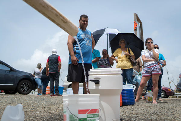 People fill containers with water from a stream near the Puerto Rico Highway 52 in Cayey on Tuesday. People have been without water service in their homes after Hurricane Maria roared through a week ago.