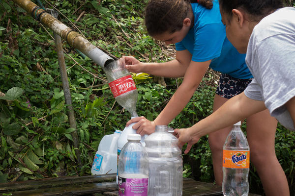 People fill plastic containers with water from a stream in Cayey, Puerto Rico. Bottled water isn't easy to get. Some stores have water in stock, but the lines are massive.