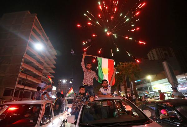 Iraqi Kurds wave the Kurdish flag as they celebrate in the streets of the northern city of Irbil on Monday following a referendum on independence.