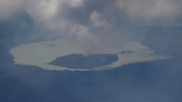 Columns of smoke billow from the crater of an erupting volcano on Vanuatu's Ambae island, in a photo from Tuesday that was provided by the New Zealand Defense Force. Fears of a strong eruption have forced a mass evacuation on Ambae.