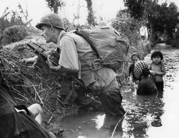 In this Jan. 1, 1966 file photo, a Paratrooper of the 173rd U.S. Airborne brigade crouches with women and children in a muddy canal as intense Viet Cong sniper fire temporarily pins down his unit during the Vietnamese War near Bao trai in Vietnam. Filmmaker Ken Burns said he hopes his 10-part documentary about the War, which begins Sept. 17, 2017 on PBS, could serve as sort of a vaccine against some problems that took root during the conflict, such as a lack of civil discourse in America. (Horst Faas/AP)