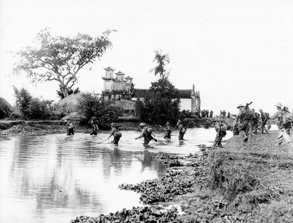 With an ancient pagoda in the background, soldiers of the French-Indochinese Union army push forward across a river towards Song Tra Ly, during war operations against Communist Viet Minh rebels, in the Tonkin region, on Dec. 31, 1954. (AP Photo)