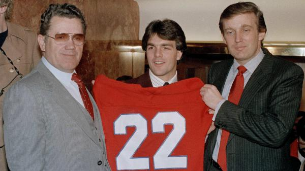 Boston College quarterback Doug Flutie poses with New Jersey Generals head coach Walt Michaels (left) and Generals owner Donald Trump at a news conference in New York on Feb. 5, 1985.