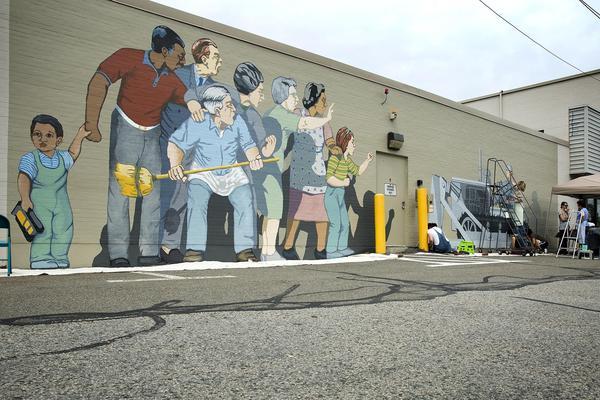 "Artist work to restore Bernie LaCasse's ""Beat the Belt"" mural in Cambridgeport this summer. (Robin Lubbock/WBUR)"