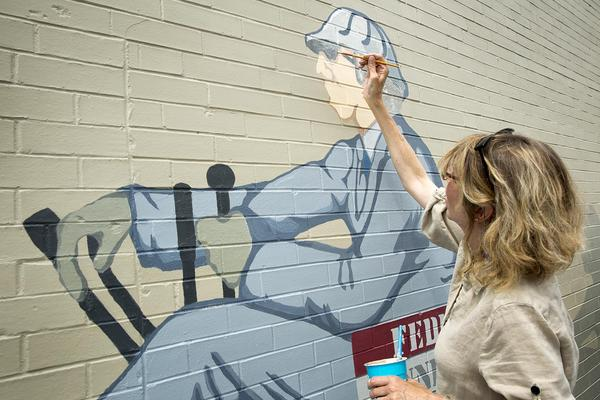 Artist Karen Wolff, a collections care specialist, works on restoration of the mural this summer. (Robin Lubbock/WBUR)