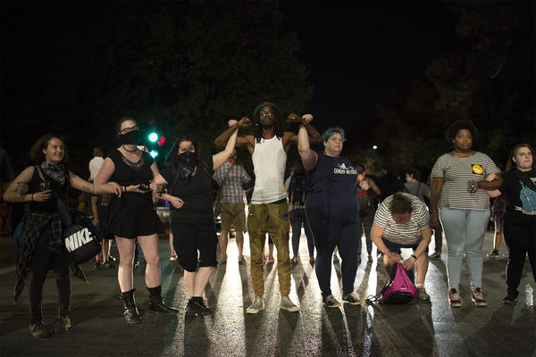 Protesters stand together on Kingshighway Friday night as police officers in riot gear move toward them.