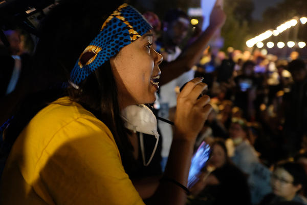 Activist LaShell Eikerenkoetter speaks to protesters before a moment of silence at Maryland and Euclid in the Central West End Friday night.