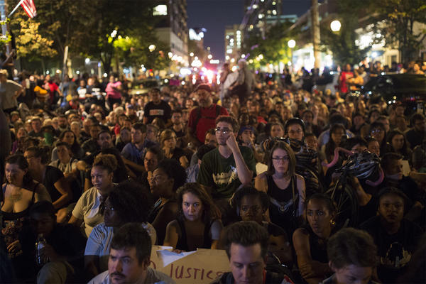 Protesters sit at the intersection of Maryland and Euclid for a moment of silence on Friday night.