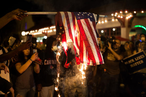 Protesters burn an American flag while demonstrating against the acquittal of Jason Stockley in the Central West End on Friday.