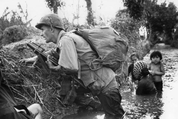In this Jan. 1, 1966 file photo, a Paratrooper of the 173rd U.S. Airborne brigade crouches with women and children in a muddy canal as intense Viet Cong sniper fire temporarily pins down his unit during the Vietnamese War near Bao trai in Vietnam. (Horst Faas/AP)