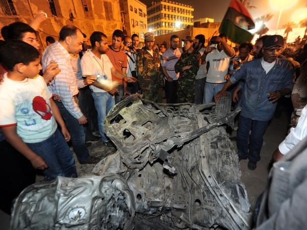 Libyan rebels gather around the remains of a car that exploded in Benghazi on Tuesday. There were no confirmed casualties, but the explosion — and others around the rebel stronghold — have unsettled nerves in the city.