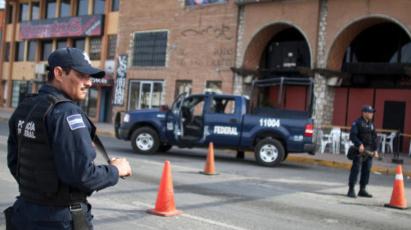 Mexican federal police man a checkpoint in downtown Juarez, Mexico, on July 13. Despite being hard hit by drug violence, Mexican border cities remain attractive to foreign businesses seeking cheap labor and easy access to the U.S.