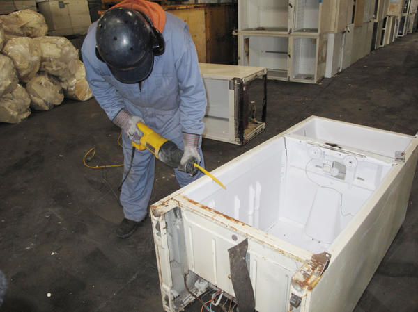 A worker at Jaco Environmental saws into an old refrigerator to remove the insulating foam in the fridge's walls. The 10 pounds of foam contains about 1 pound of CFC 11 gas, a very powerful greenhouse gas. Jaco sends the foam and other CFCs in the fridge's compressor to be destroyed.