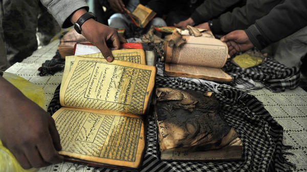 On Feb. 21 outside Bagram Airfield, Afghan demonstrators show copies of Qurans allegedly set on fire by U.S. soldiers at a NATO airbase outside Kabul.