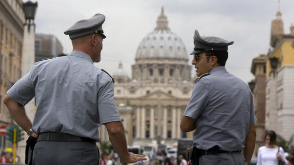 Italian financial police officers talk in front of St. Peter's Basilica in Rome. Recently leaked Vatican documents have raised questions about the Vatican's financial transactions.