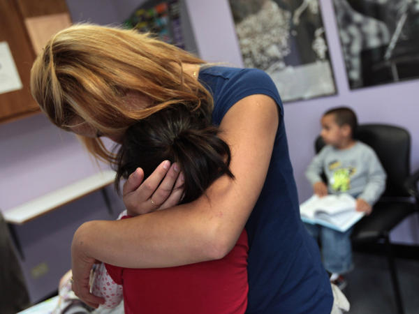 Many working mothers say their employers don't support them when they need to tend to a sick child. In this file photo, a single mother holds her child at a health clinic in Colorado.