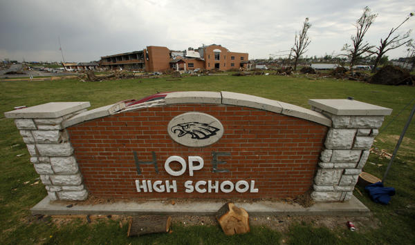 "In this photo taken June 14, 2011, a damaged sign for Joplin High School (transformed into ""hope"" with tape) is seen in front of the school. The school was one of three in the city destroyed by an EF-5 tornado that wiped out much of the community."
