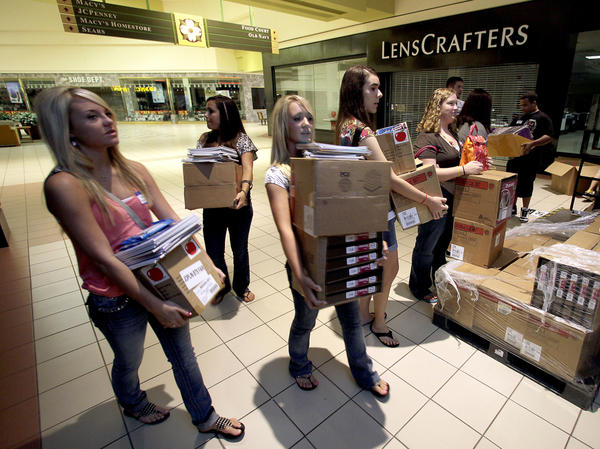 Students carry donated supplies to a classroom on the first day of school at a temporary high school in a converted big-box store in Joplin, Mo., last August. School started on time in the district nearly three months after an EF-5 tornado devastated much of the city and killed 161 people.