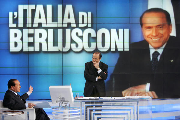 "Berlusconi (left) answers journalist Bruno Vespa's questions during a broadcast of ""Porta a Porta,"" an Italian TV talk show in 2006."