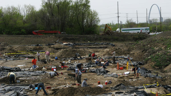 Archaeologists and crew members from the Illinois State Archaeological Survey work at an East St. Louis dig site, which is believed to be a suburb of the ancient city of Cahokia. Black plastic sheeting protects the excavations. In the distance, construction crews are building a stretch of interstate freeway leading to a new Mississippi River bridge.