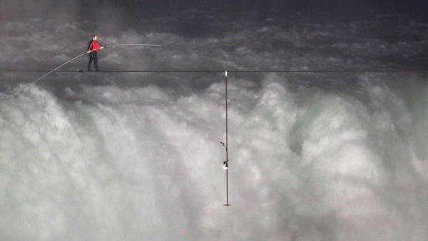 Nik Wallenda crosses over  Niagara Falls on a tightrope on Friday. He became the first person to cross directly over the falls from the U.S. into Canada.
