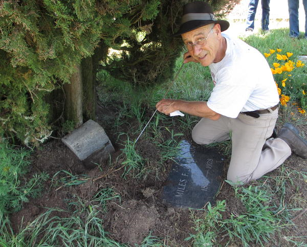 "Tony Pires uses a metal rod to find a grave marker. Decades of growing plants, pecking birds and digging gophers can make things strangely ""disappear"" in old cemeteries like Gilliam."