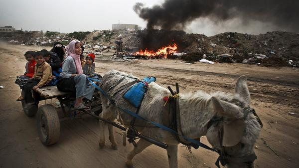 A Palestinian family rides on a donkey cart along a waste dump in Al-Nusirat, central Gaza Strip, in February. Living conditions continue to deteriorate for the 1.8 million Palestinians who reside in Gaza.
