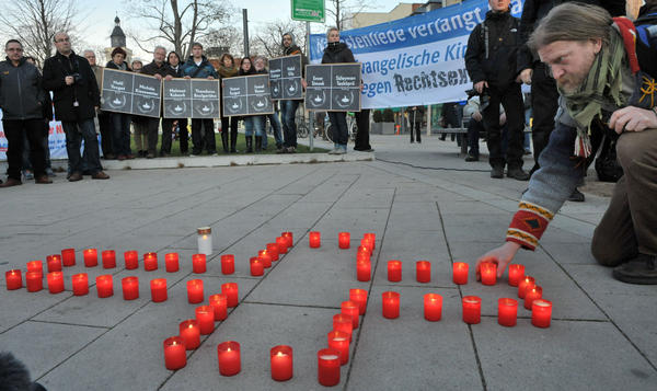 A man lights candles during a Nov. 28 commemoration vigil in the eastern German town of Erfurt for the victims of murders allegedly committed by a right-wing extremist group with ties to the NPD.