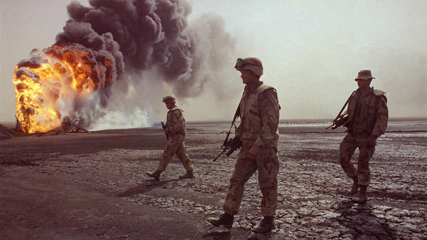 A U.S. Marine patrol walks across the charred oil landscape near a burning well near Kuwait City in March 1991. Concerns about oil supply were at play when the U.S. and its allies intervened during the Iraqi invasion of Kuwait in 1990. But American policy is changing now that Mideast oil imports to the U.S. are declining.